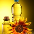 Cooking oil in a plastic and glass bottles with sunflower. - Stock Photo
