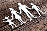 Cardboard figures of the family on a wooden table. — Stock Photo