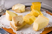 Variety of cheeses on a lace napkin. — Stock Photo