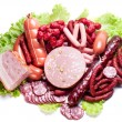 Meat and sausages on lettuce leaves. — Stock Photo