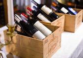 Wijn flessen in houten kisten. — Stockfoto
