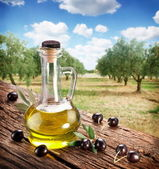 Black olives with bottle of oil on a wooden table. — Stock Photo