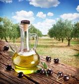 Azeitonas pretas com garrafa de óleo sobre uma mesa de madeira. — Foto Stock