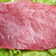Raw meat on lettuce leaves. - Zdjcie stockowe