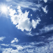 Blue sky with clouds and sun. - Foto de Stock