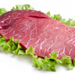 Raw meat on lettuce leaves. - 图库照片