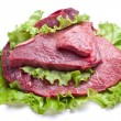 Raw meat on lettuce leaves. - Stock Photo