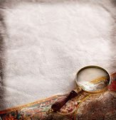 Magnifying glass on old parchment. — Stock Photo