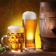 Beer glasses with a wooden barrel. — Stock Photo