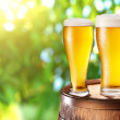 Two glasses of beer on a wooden barrel. — Stock Photo