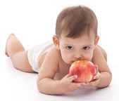 Baby girl attacking an apple. — Stock Photo