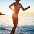 Sexy athletic woman running on the beach. - Stock Photo