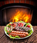 Steak, sausage and vegetable on a plate — Stock Photo