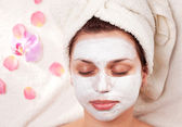 Young woman with clay facial mask in beauty salon. — Stock Photo