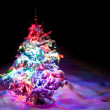 Luminous New Year's tree under powder snow.  — Stock Photo