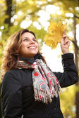 Young smiling woman in the autumn park. — Stock Photo
