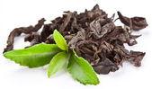 Tas de thé sec avec du thé vert feuilles. — Photo