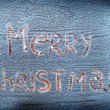 Words Merry Christmas written over snowy desk. — Lizenzfreies Foto