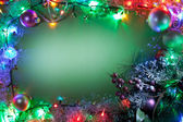 Christmas frame with fairy lights and baubles. — Stock Photo