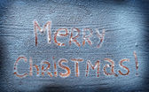 Words Merry Christmas written over snowy desk. — Stock Photo