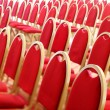 Stock Photo: Ranges of empty red chairs.