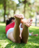 Smiling young woman sits on the grass. — Stock Photo