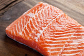 Salmon filet on a wooden carving board. — Foto Stock