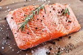 Salmon filet on a wooden carving board. — Stock fotografie