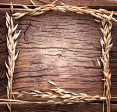 Ears of wheat made as frame on old wooden table. — Stock Photo