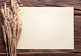 Ears of wheat and sheet of paper on old wooden table. — Stock Photo