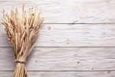 Ears of wheat on old wooden table. — Stock Photo