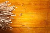 Oren van tarwe op oude houten tafel. — Stockfoto