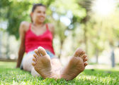 Young woman on the grass. The face in defocus. — Stock Photo