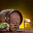 Beer glass, old oak barrel, wheat ears and hops. — Stock Photo #44413887