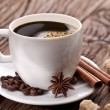 Cup of coffee with coffee beans and spices near it. — Stock Photo