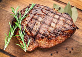 Beef steak on a wooden table. — Stock Photo