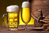 Beer glasses, old oak barrel and wheat ears. — Stock Photo