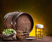 Beer glass, old oak barrel, wheat ears and hops. — Stock Photo