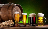 Beer glasses, old oak barrel and wheat. — Stock Photo