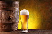 The glass of beer near woden barrel. — Stock Photo