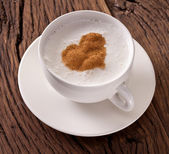 Cup of cappuccino with ground cinnamon in the form of heart. — Stock Photo