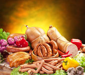 Still-life with sausage products, vegetables and herbs. — Stock Photo