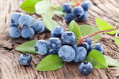 Blueberries with leaves on a wooden table. — Stock Photo