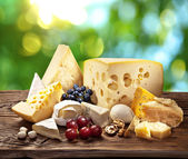 Different types of cheese over old wooden table. — Stockfoto
