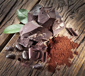 Chocolate and cocoa bean over wooden table. — Stock Photo
