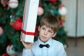 Schoolboy with gifts at Christmas tree — Stock Photo