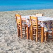 Greek taverna table and chairs on sandy beach - Stock Photo