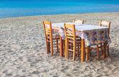 Greek taverna table and chairs on sandy beach — Stock Photo