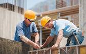 Obreros trabajando en marcos de cemento encofrado — Foto de Stock