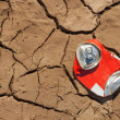 Empty soda can on dry soil — Stok fotoğraf